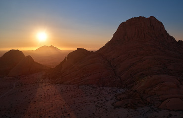 Panoramic, aerial view on a silhouette of a ancient Spitzkoppe mountain against sunset. Rocky desert landscape. Travelling to remote place in Namibia.