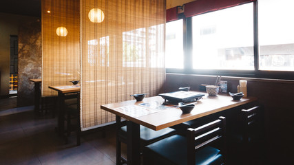 Shabu dining table set including one wooden table and four seats with bamboo wall for privacy.