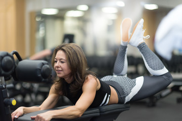 Beautiful middle age athletic woman doing some crunches for her back on a bench at the gym