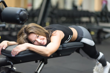 Beautiful middle age athletic woman have a rest on a bench at the gym