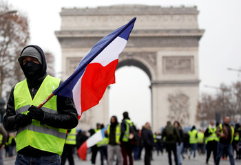 "Protesters wearing yellow vests take part in a demonstration by the ""yellow vests"" movement in Paris"