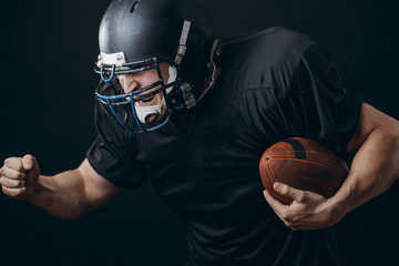American football caucasian player wearing black uniform with protection holding ball isolated over black studio wall