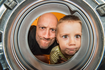 Portrait of father and son view from washing machine inside. What is that thing inside the washing machine?