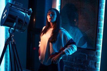 awesome brown-haired girl in the dark room. youth, fashion, beauty concept . closeup photo. sports clothes. girl is dressed sharp