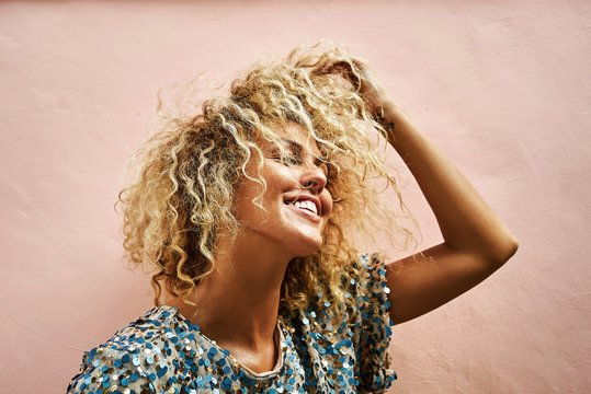 portrait of an attractive blonde female smiling and touching her hair curly hair in pink wall background