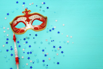 carnival party celebration concept with elegant red mask on stick over mint wooden background and stars. Top view.
