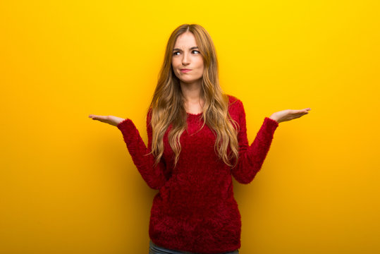 Young girl on vibrant yellow background having doubts while raising hands and shoulders