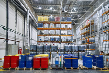 Oil drums and plastic container on pallets in a warehouse on metal shelving. Handling and storing industrial lubricants. Hazardous material storage. Red and blue tank