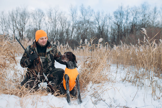 hunter and dog are in the winter forest. close up photo.copy space. holiday with friend.happy moments with a pet