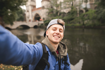 Young lucky tourist makes a sephi on the background of the lake and the castle and smiles. Young man in a cap takes selfie in autumn park.