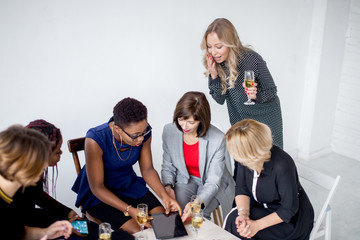 Young Women Entrepreneurs, participating in workshops, discuss rising questions after a business meeting. Formally dressed females celebrate a successful project with alchohol.