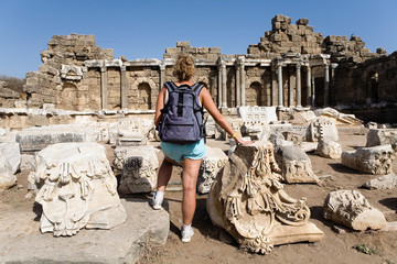 The girl traveler admires the ruins of the ancient city.