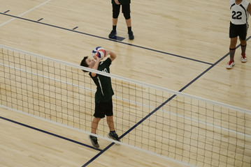 Volleyball player setting the ball by the net