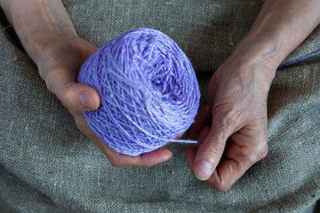 A ball of thread in the hands of an elderly woman.