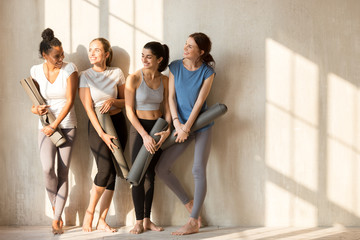 On a sunny morning beautiful diverse girls gathered at gym for workout. Four slim women in sportswear standing barefoot near wall holding yoga mats talking feels happy. Group training wellness concept