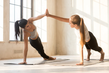 Young attractive blond and brunette diverse multi-ethnic women practicing yoga together giving high five holding hands and standing in side plank pose on rubber mats at fitness studio in the morning.