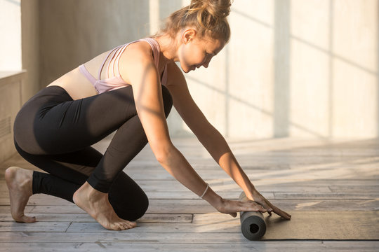 Attractive yoga instructor is preparing for session unrolling rubber carpet in light cozy room. Sportive woman wearing sport bra and pants finished workout folding mat after training at fitness club
