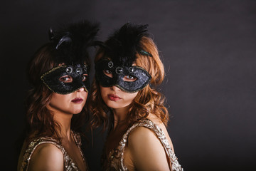 Portrait of two women dancers in max-size masks and gold dresses