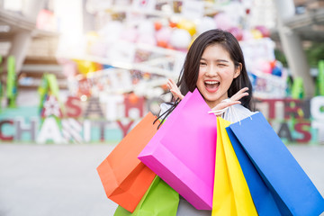 Happiness, Consumerism, Smiling young woman with shopping bags in the travel city