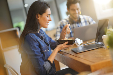 Beautiful woman eating lunch whilst working in co working space Fototapete