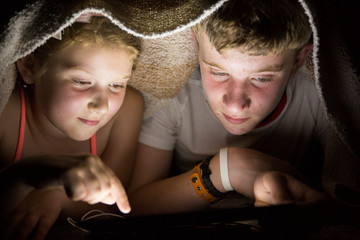 Boy and girl using a tablet at night under a blanket