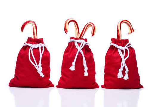 Three red Santa Toy Bags with  a draw string cinching the bags closed