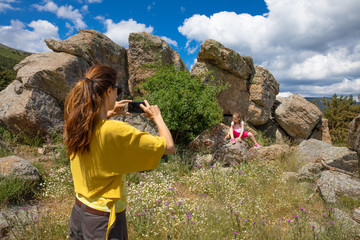 woman taking a photo or video recording with smartphone to her daughter, four years old girl, sitting on rock in Navafria (Guadarrama Natural Park, Madrid, Spain, Europe)
