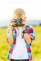 Young blonde boy holding a camera