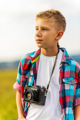 Potrait of a young blonde boy holding a camera