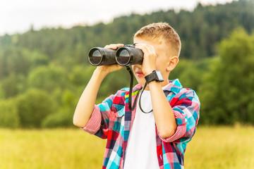 Young blonde boy looking through binoculars