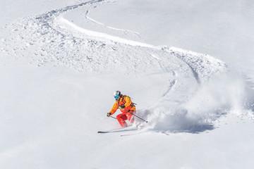 freeride skier skiing downhill through deep powder snow