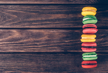 Row of sweet macaroons on wooden table.