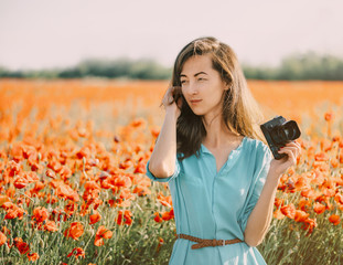 Photographer beautiful woman standing in poppy meadow.