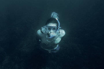 Man swimming underwater in deep sea.