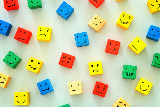 concept of Different emotions drawn on colorfull cubes, wooden background.