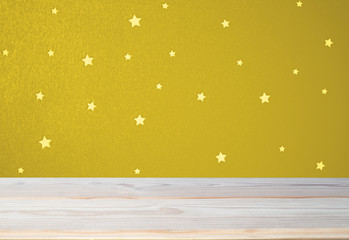 pastel beautiful golden wall with stars and empty wooden tabletop in childrens room