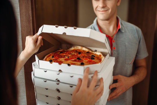 Delivery man shows pizza to customer at the door