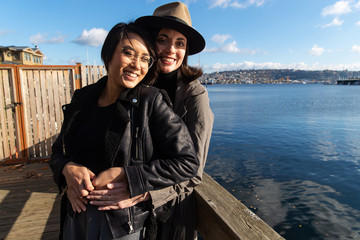 Lesbian couple holding each other near a body of water