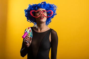 Woman wearing blue wig holding toy gun