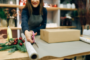 Female person cuts wrapping paper, gift decoration