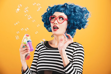 Colorful portrait of woman with bright blue hair blowing and popping bubbles