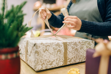 Female person ties a gold bow on gift box