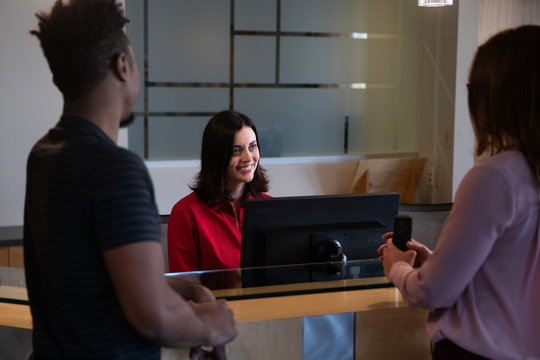Friendly receptionist greeting guests in office lobby