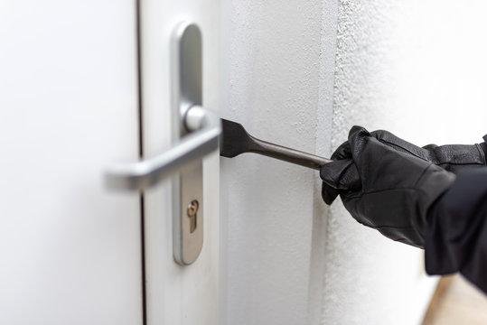 Einbrecher will mit einer Brechstange eine Haustür aufhebeln