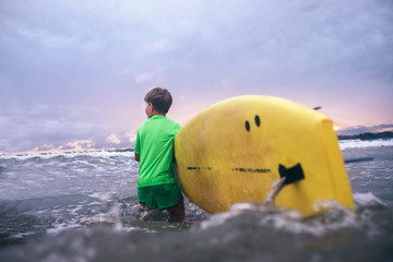 Little boy carries yellow surf board into ocean waves. Surfing First steps concept.