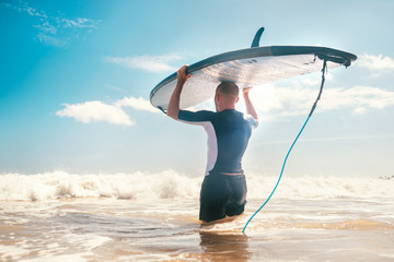 Young Man surfer with long board on head goes to the sea to have a surf practice. Learning surfing concept.