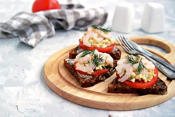 Rye open sandwich with tomato, egg salad and shrimps. Danish cuisine.