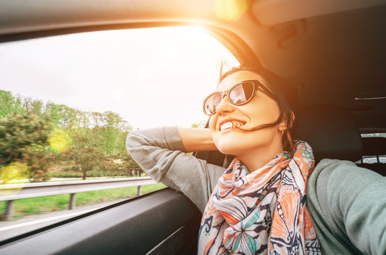 Woman enjoy with view from car window when traveling by auto