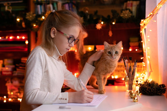 Blonde child girl with big pink and black glasses writing letter to the Santa Claus or drawing something on the background with warm yellow bokeh. Christmas and New Year theme
