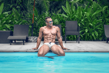 Muscular young sexy wet naked guy near the pool in a speedo